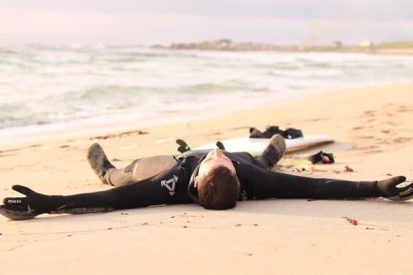 Surfer i xcel våtdrakt utmattet