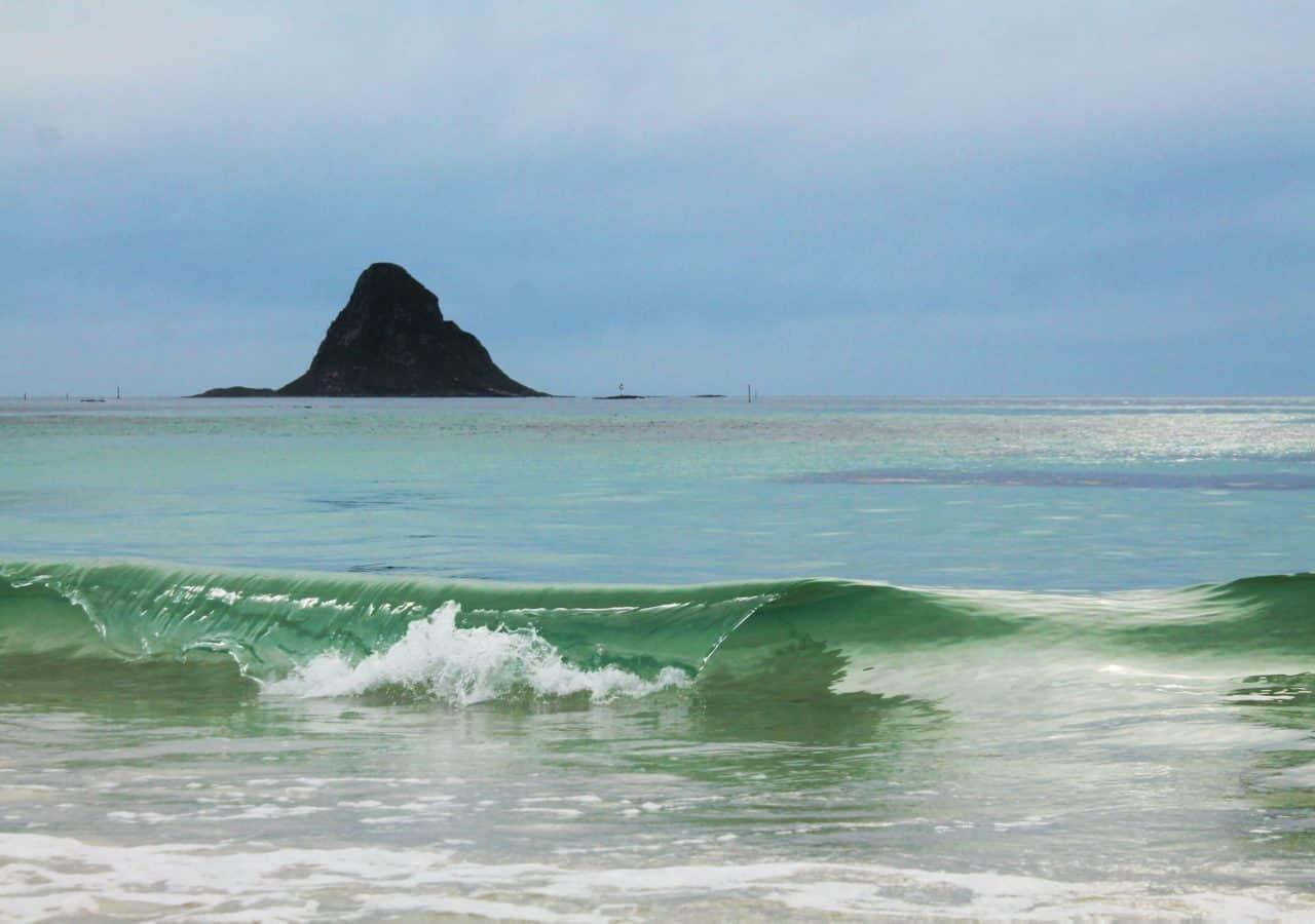 """Bildet er tatt 1.juli på Bleikstranda, Andøya. Fjellet i bakgrunnen er slående likt Chinamans Hat på Oahu, Hawaii, for de av dere som har vært der. Jeg synes det var gøy å leke med tanken som at denne nydelige shorebreaken hadde vært Hawaii klasse om den hadde vært omtrent ti ganger større. Det kan være tøft å være surfer om sommeren når havet er flatt, men det er godt man kan """"mind-surfe"""" litt en gang i blant. Tina Paasche"""