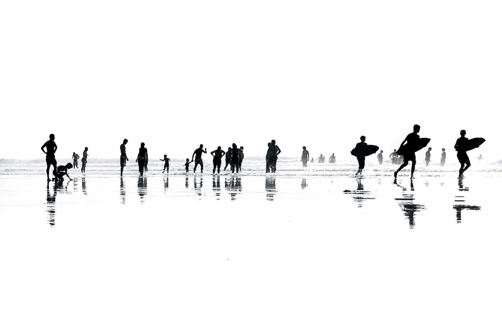 Svart hvitt bilde av mye folk på stranda