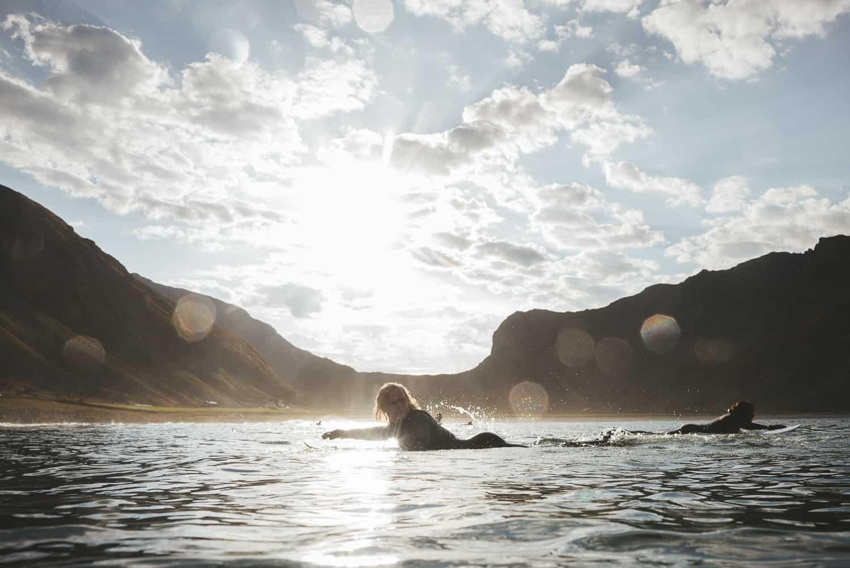 Surfer padler i vannet på Unstad.