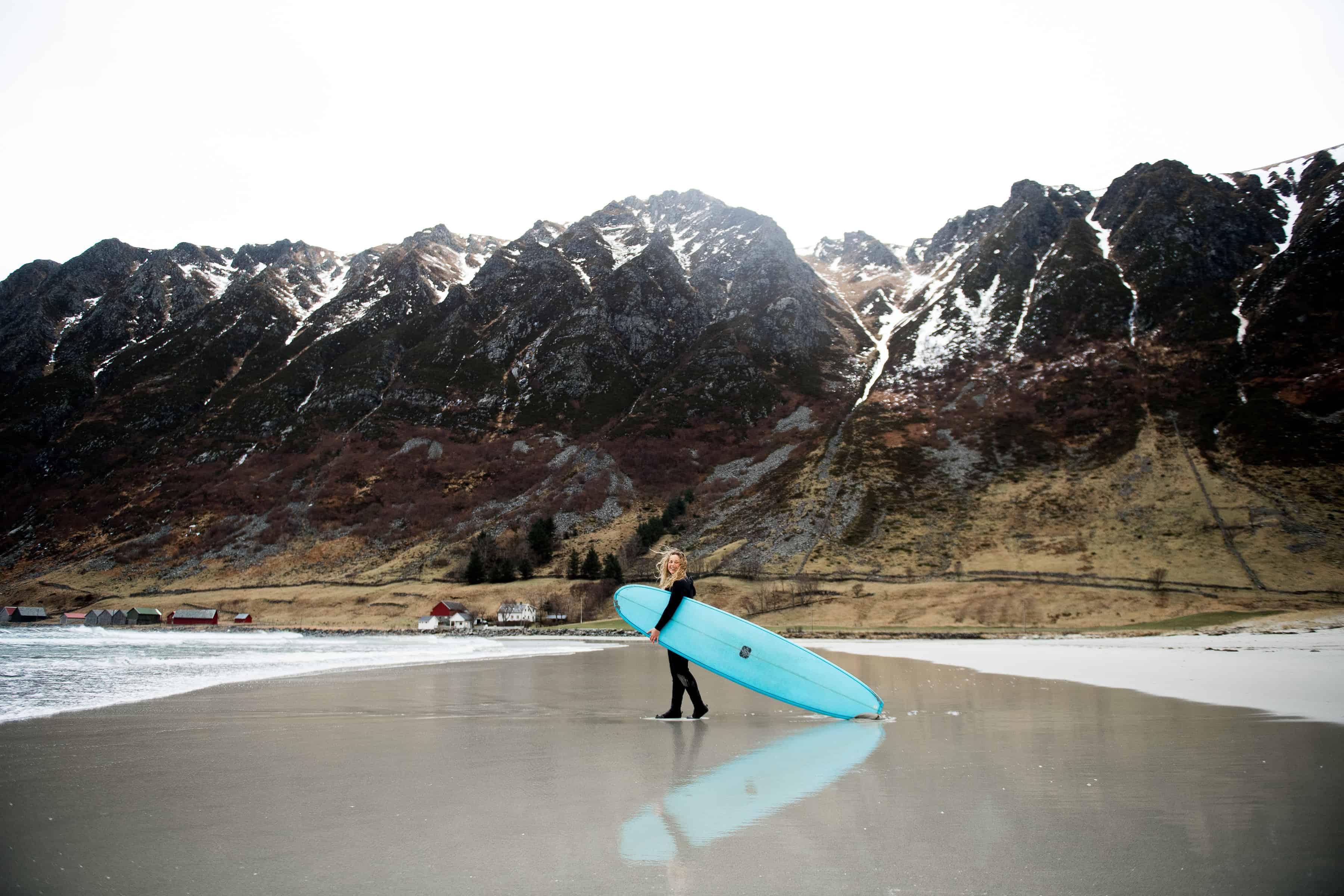 Jente med blått longboard på stranda i Hoddevik.