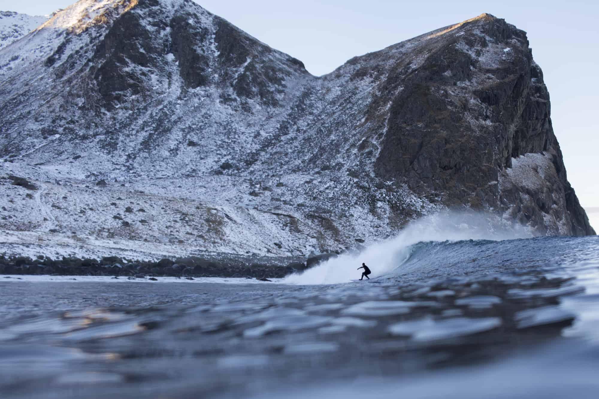 Joel Stevenson surfer i Lofoten blant store fjell.