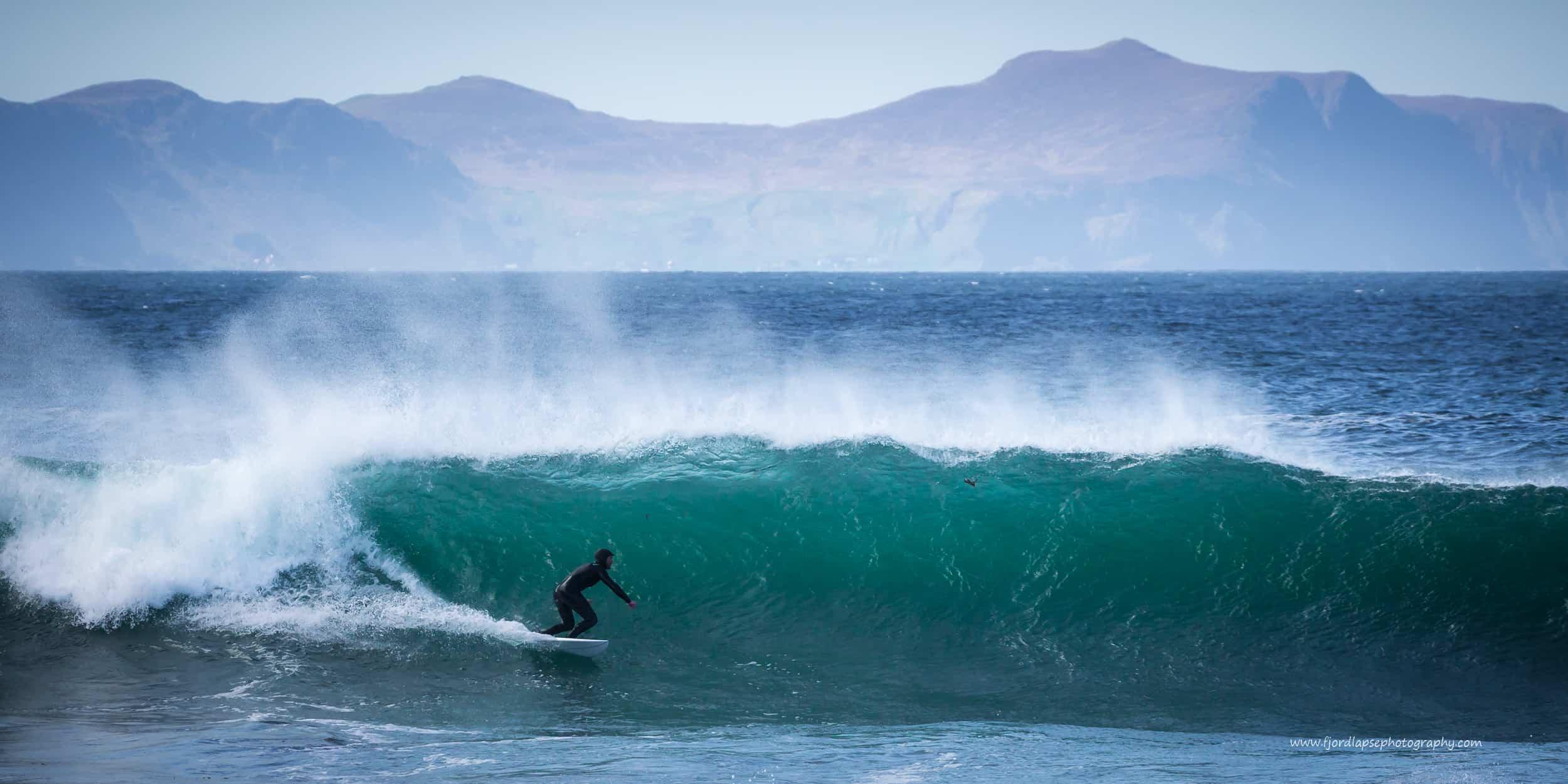 Surfer bølge på Sunnmøre. Fjell i bakgrunnen.