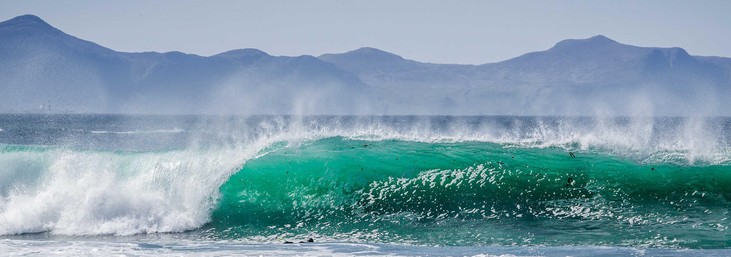Surfer padler ut mot stor bølge.