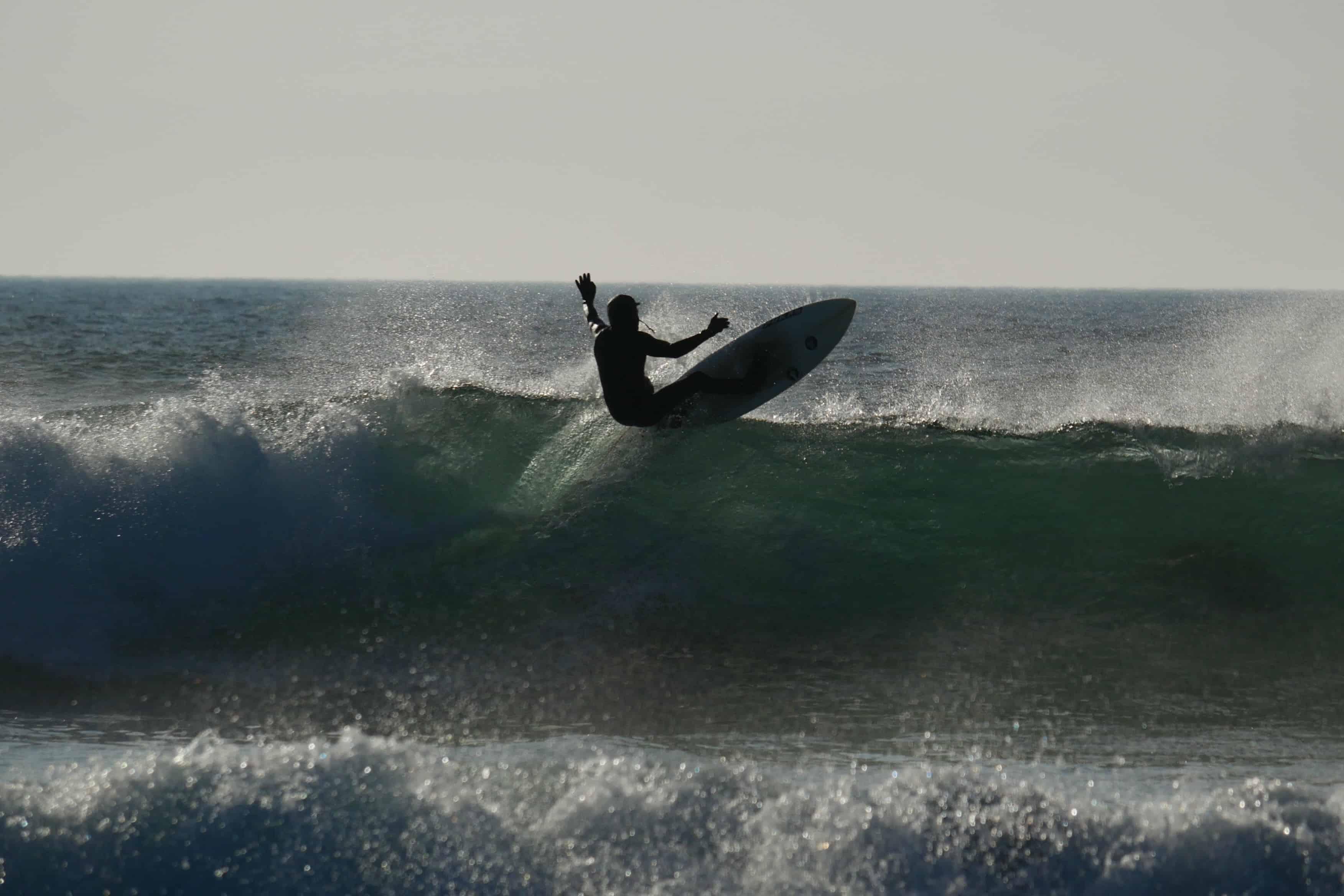Siluett av surfer i bølge.