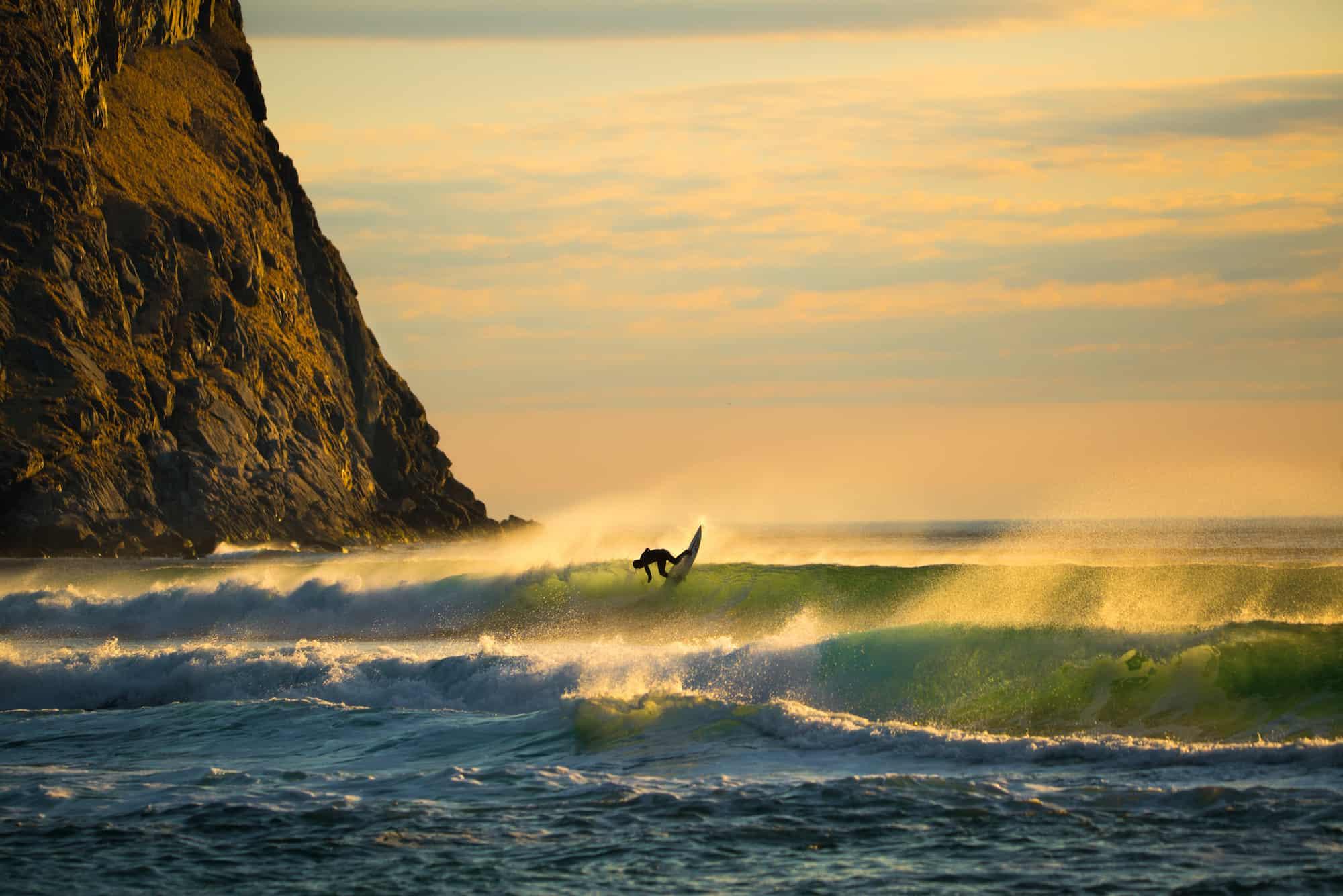 Surfer i nydelig lys og fine bølger.