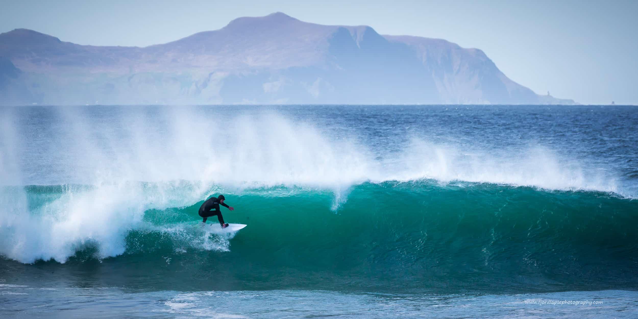 Milde mai! Surfer i bølge på Sunnmøre.