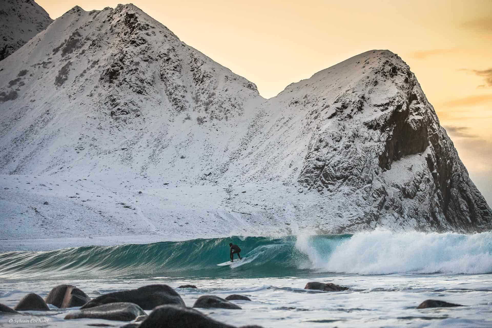 Surfer på Unstad i solnedgang.