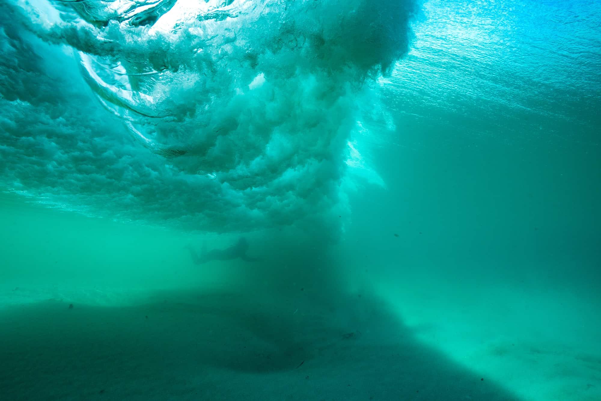 Surfer duckdiver gjennom bølge