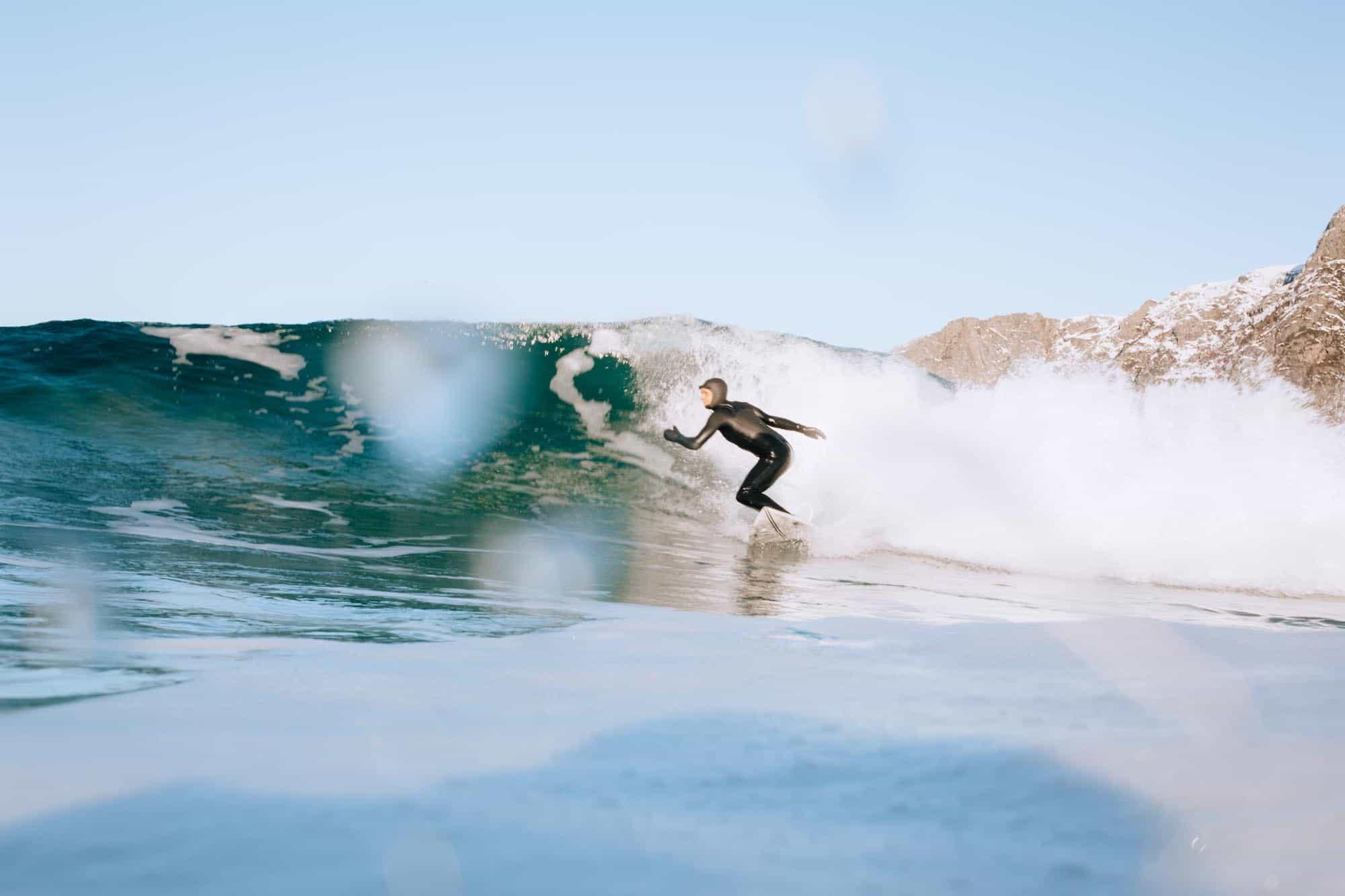 Heidi Neerby bottom turn med snølagte fjell i bagrunnen